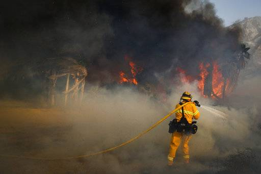 A firefighter battles a wildfire at Faria State Beach in Ventura, Calif., Thursday, Dec. 7, 2017. The wind-swept blazes have forced tens of thousands of evacuations and destroyed dozens of homes.