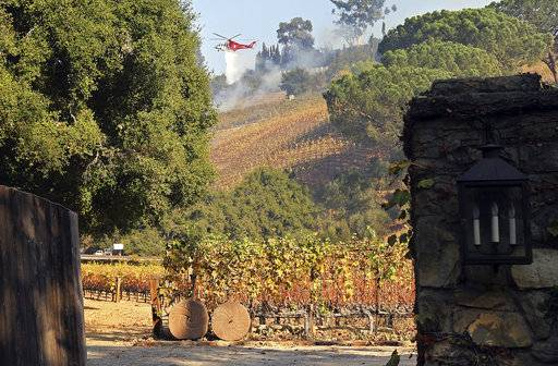 In this Wednesday, Dec. 6, 2017 photo, a Los Angeles Fire Department helicopter makes a water drop on media mogul Rupert Murdoch's 16-acre (6.5-hectare) Moraga Vineyards estate, where about 7 acres (2.8 hectares) of vines appeared to have been damaged, a spokeswoman said.