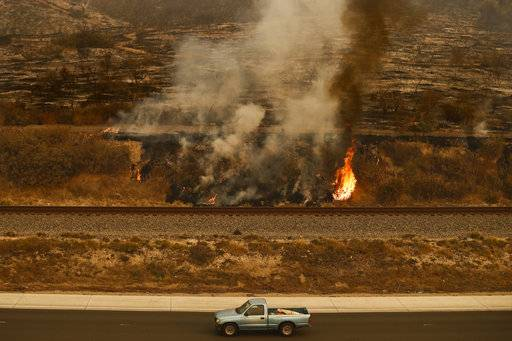 A pickup truck passes a wildfire burning along the 101 Freeway in Ventura, Calif., Thursday, Dec. 7, 2017. The wind-swept blazes have forced tens of thousands of evacuations and destroyed dozens of homes.