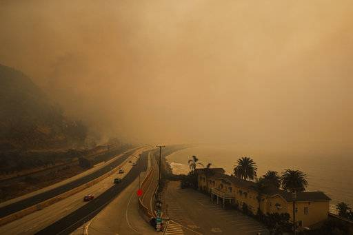 Traffic moves along the 101 Freeway as smoke from a wildfire fills the air in Ventura, Calif., Thursday, Dec. 7, 2017. The wind-swept blazes have forced tens of thousands of evacuations and destroyed dozens of homes.
