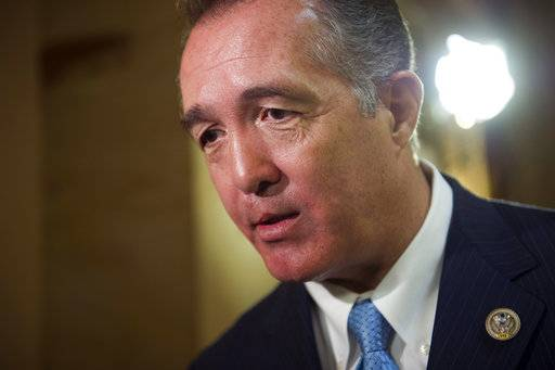FILE - In this March 24, 2017, file photo, Rep. Trent Franks, R-Ariz. speaks with a reporter on Capitol Hill in Washington. Franks says he is resigning Jan. 31 amid a House Ethics Committee investigation of possible sexual harassment. Franks says in a statement that he never physically intimidated, coerced or attempted to have any sexual contact with any member of his congressional staff. Instead, he says, the dispute resulted from a discussion of surrogacy. Franks and his wife have 3-year-old twins who were conceived through surrogacy.