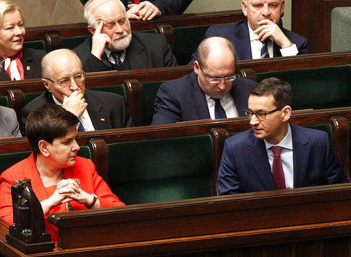 In this Dec. 5, 2017 photo Poland's Prime Minister Beata Szydlo, front left and Finance Minister Mateusz Morawiecki, front right, attend a parliament session in Warsaw, Poland.  Poland's conservative ruling party said Thursday, Dec. 7, 2017, that Prime Minister Szydlo, has resigned and will be replaced by Morawiecki.