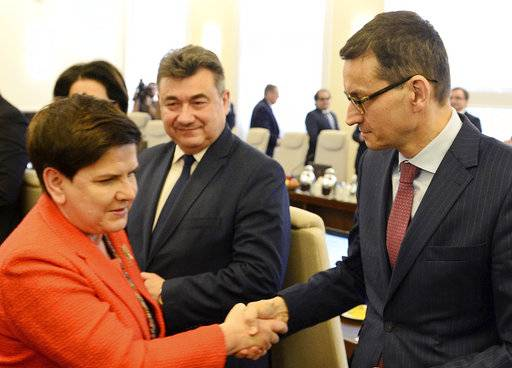 In this Dec. 5, 2017 photo Poland's Prime Minister, Beata Szydlo, left, shakes hands with Finance Minister, Mateusz Morawiecki, right, prior to a government meeting in Warsaw, Poland, Tuesday, Dec. 5, 2017. Poland's conservative ruling party says Szydlo has resigned and will be replaced by Morawiecki.