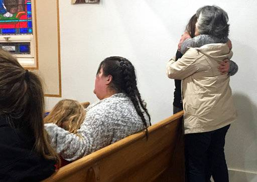 People gather for a vigil at St. Joseph Church in Aztec, N.M., Thursday, Dec. 7, 2017. Students hid in their classrooms, some behind locked doors or in closets, as a gunman opened fire Thursday inside a New Mexico high school.