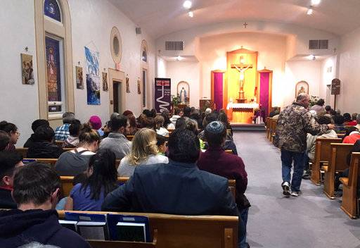 People gather for a vigil at St. Joseph Church in Aztec, N.M., Thursday, Dec. 7, 2017,  Students hid in their classrooms, some behind locked doors or in closets, as a gunman opened fire Thursday inside a New Mexico high school,