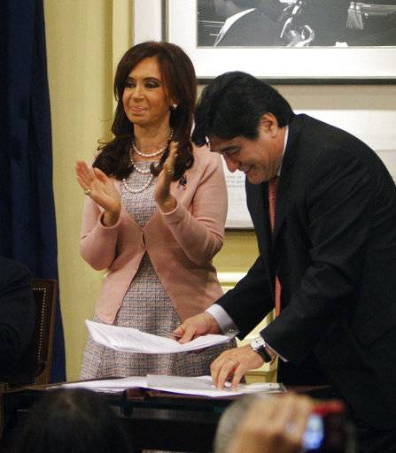 FILE - In this July 21, 2010 file photo, Argentina's President Cristina Fernandez, left, applauds after signing the same sex marriage bill at the government house accompanied by presidential legal aid Carlos Zannini, in Buenos Aires, Argentina. An Argentine judge on Thursday, Dec. 7, 2017, accused Fernandez of the crime of treason as he asked lawmakers to remove Fernandez's immunity from prosecution as a senator. The judge has also ordered the arrest of Zannini.