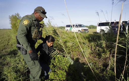In this Aug. 11, 2017, photo a U.S. Customs and Border Patrol agent escorts an immigrant suspected of crossing into the United States illegally along the Rio Grande near Granjeno, Texas. The election of President Donald Trump contributed to a dramatic downturn in migration, causing the number of arrests at the border to hit an all-time low in April. But since then, the number of immigrants caught at the southern border has been increasing monthly.