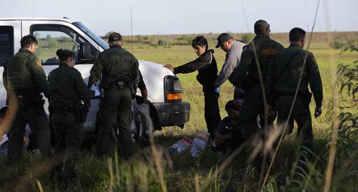 In this Aug. 11, 2017, photo, immigrants suspected of crossing into the United States illegally along the Rio Grande near Granjeno, Texas, are held by U.S. Customs and Border Patrol agents. The election of President Donald Trump contributed to a dramatic downturn in migration, causing the number of arrests at the border to hit an all-time low in April. But since then, the number of immigrants caught at the southern border has been increasing monthly.