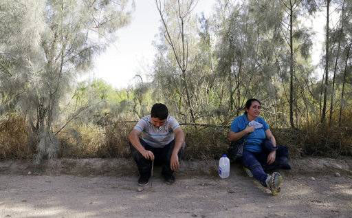 In this Aug. 11, 2017, photo, over heated immigrants suspected of crossing into the United States illegally along the Rio Grande near Granjeno, Texas, are held by U.S. Customs and Border Patrol agents. The election of President Donald Trump contributed to a dramatic downturn in migration, causing the number of arrests at the border to hit an all-time low in April. But since then, the number of immigrants caught at the southern border has been increasing monthly.