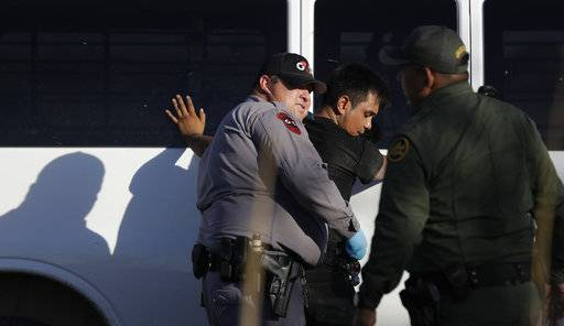 In this Aug. 11, 2017, photo, immigrants suspected of crossing into the United States illegally along the Rio Grande near Granjeno, Texas, are held by U.S. Customs and Border Patrol agents. The election of President Donald Trump contributed to a dramatic downturn in migration, causing the number of arrests at the border to hit an all-time low in April. Since then, the number of immigrants caught at the southern border has been increasing monthly.