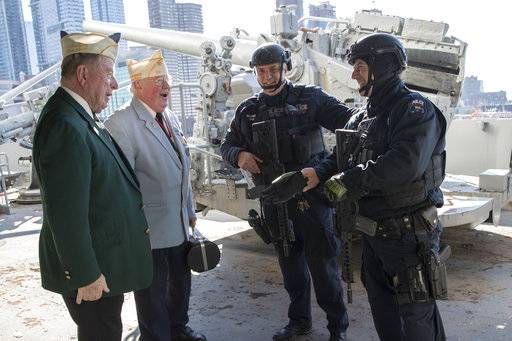Veterans John Dunleavy, left, and Jim Mullarkey, second from left, speak to heavily armed police officers during a ceremony commemorating the 76th anniversary of the Dec. 7, 1941 Japanese attack on Pearl Harbor, Thursday, Dec. 7, 2017, on board the Intrepid Sea, Air & Space Museum in New York.