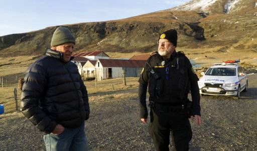 Police inspector Adolf Arnason talks with a local farmer living at the foot of Oraefajokull volcano in Iceland, Thursday, Nov. 30, 2017. The Oraefajokull volcano, dormant since its last eruption in 1727-1728, has seen a recent increase in seismic activity and geothermal water leakage that has worried scientists. With the snow hole on Iceland's highest peak deepening 18 inches (45 centimeters) each day, authorities have raised the volcano's alert safety code to yellow.