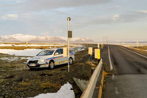 A police car is parked by the side of the road at the foot of Oraefajokull volcano in Iceland, Thursday, Nov. 30, 2017. The Oraefajokull volcano, dormant since its last eruption in 1727-1728, has seen a recent increase in seismic activity and geothermal water leakage that has worried scientists. With the snow hole on Iceland's highest peak deepening 18 inches (45 centimeters) each day, authorities have raised the volcano's alert safety code to yellow.