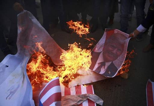 Palestinians burn a poster of U.S. President Donald Trump and a representation of an American flag, during a protest against the U.S. decision to recognize Jerusalem as Israel's capital, in Gaza City Thursday, Dec. 7, 2017.