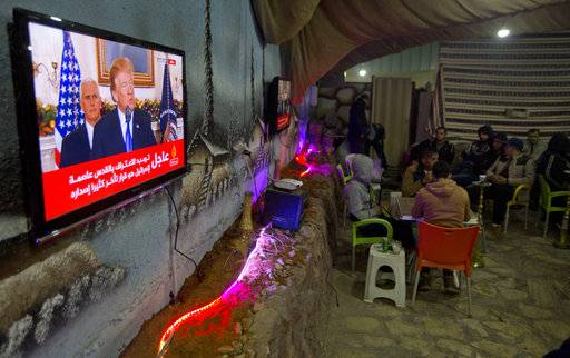 Palestinians play cards during U.S. President Donald Trump's televised speech in the West Bank City of Nablus, Wednesday, Dec. 6, 2017. Defying dire, worldwide warnings, President Donald Trump on Wednesday broke with decades of U.S. and international policy by recognizing Jerusalem as Israel's capital.