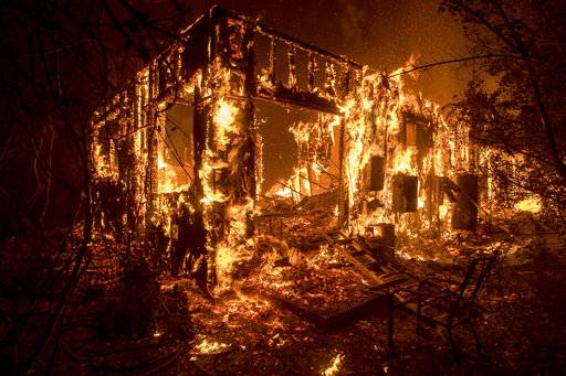 Flames consume a home as a wildfire burns in Ojai, Calif., on Thursday, Dec. 7, 2017.
