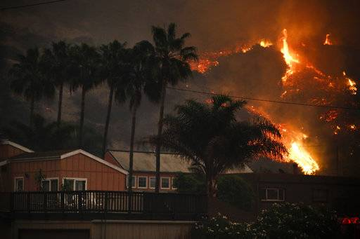 A wildfire threatens homes as it burns along a hillside in La Conchita, Calif., Thursday, Dec. 7, 2017. The wind-swept blazes have forced tens of thousands of evacuations and destroyed dozens of homes.