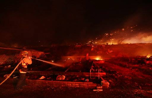 Fire crews work among destroyed homes at the Rancho Monserate Country Club community Thursday, Dec. 7, 2017, in Fallbrook, Calif. The wind-swept blazes have forced tens of thousands of evacuations and destroyed dozens of homes in Southern California.