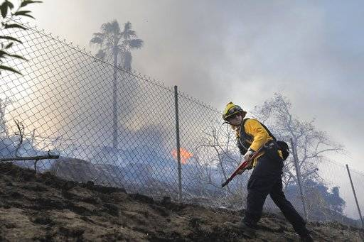 "A Vista firefighter cuts a hole in a fence at a home on West Lilac Road in Bonsall, Calif., Thursday, Dec, 7, 2017.  The biggest and most destructive of the windblown fires raking Southern California shut down one of the region's busiest freeways Thursday and threatened Ojai, a scenic mountain town dubbed ""Shangri-La� and known for its boutique hotels and New Age spiritual retreats.  (Howard Lipin/The San Diego Union-Tribune via AP)"