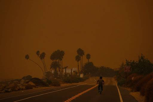 A man rides his bicycle along the Pacific Coast Highway as thick smoke from a massive wildfire fills the air at Faria State Beach in Ventura, Calif., Thursday, Dec. 7, 2017. The wind-swept blazes have forced tens of thousands of evacuations and destroyed dozens of homes.