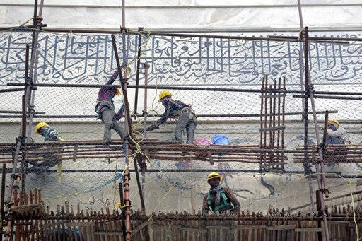 In this Tuesday, Dec. 5, 2017, photo, workers peel off the application of fuller's earth or locally called multani mitti from the walls of the Taj Mahal during its cleaning process caused by environmental pollution in Agra, India. Authorities in India are trying to figure out how workers will scale the Taj Mahal's majestic but delicate dome as they complete the first thorough cleaning of the World Heritage site since it was built 369 years ago. Work on the mausoleum's minarets and walls is almost finished, after workers began the makeover in mid-2015. They've been using a natural mud paste to remove yellow discoloration and return the marble to its original brilliant white.