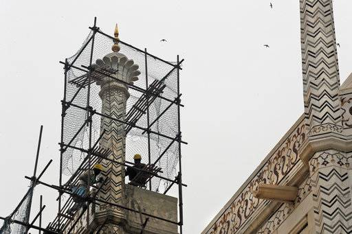 In this Tuesday, Dec. 5, 2017, photo, Indian workers clean the discoloration of the Taj Mahal caused by environmental pollution in Agra, India. Authorities in India are trying to figure out how workers will scale the Taj Mahal's majestic but delicate dome as they complete the first thorough cleaning of the World Heritage site since it was built 369 years ago. Work on the mausoleum's minarets and walls is almost finished, after workers began the makeover in mid-2015. They've been using a natural mud paste to remove yellow discoloration and return the marble to its original brilliant white.