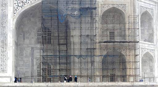 In this Tuesday, Dec. 5, 2017, photo, tourists walk past the discoloured wall of the Taj Mahal caused by environmental pollution which stands out in sharp contrast against the cleanup one in Agra, India. Authorities in India are trying to figure out how workers will scale the Taj Mahal's majestic but delicate dome as they complete the first thorough cleaning of the World Heritage site since it was built 369 years ago. Work on the mausoleum's minarets and walls is almost finished, after workers began the makeover in mid-2015. They've been using a natural mud paste to remove yellow discoloration and return the marble to its original brilliant white.