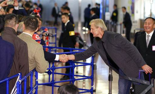 North Korean men's national soccer team head coach Jorn Andersen of Norway is greets by North Korea residents in Japan upon arrival at Haneda international airport in Tokyo Tuesday, Dec. 5, 2017. North Korean women's and men's national soccer teams arrived in Tokyo as exception to Japan's entry ban as part of ongoing sanctions against Pyongyang's missile and nuclear development. North Korea is competing against Japan, China and South Korea in the upcoming E-1 Football Championship held in Japan.