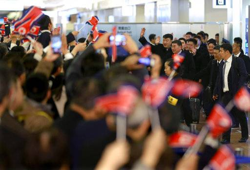 North Korean men's national soccer team members are welcomed with their national flags waved upon arrival at Haneda international airport in Tokyo Tuesday, Dec. 5, 2017. North Korean women's and men's national soccer teams arrived in Tokyo as exception to Japan's entry ban as part of ongoing sanctions against Pyongyang's missile and nuclear development. North Korea is competing against Japan, China and South Korea in the upcoming E-1 Football Championship held in Japan.