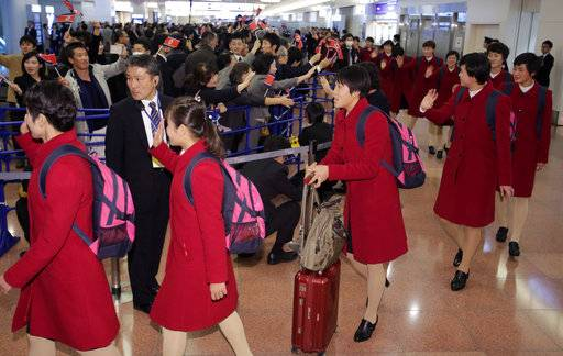 North Korean women's national soccer team members, in red, wave upon arrival at Haneda international airport in Tokyo Tuesday, Dec. 5, 2017. North Korean women's and men's national soccer teams arrived in Tokyo as exception to Japan's entry ban as part of ongoing sanctions against Pyongyang's missile and nuclear development. North Korea is competing against Japan, China and South Korea in the upcoming E-1 Football Championship held in Japan.