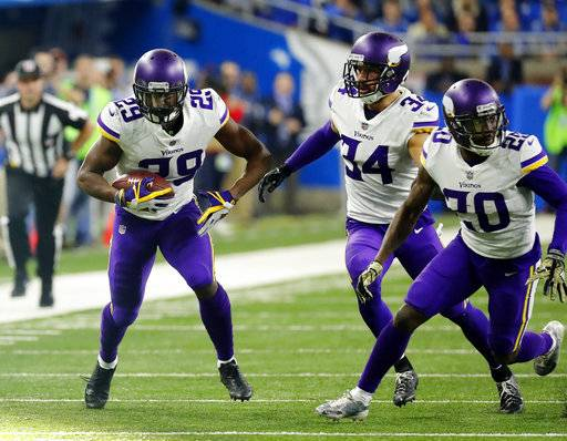 FILE- In this Thursday, Nov. 23, 2017, file photo, Minnesota Vikings cornerback Xavier Rhodes (29) returns an interception as teammates Mackensie Alexander (20) and Andrew Sendejo move into block during the second half of an NFL football game against the Detroit Lions in Detroit.  The Vikings let cornerback Captain Munnerlyn sign with the Carolina Panthers in free agency, but their pass coverage hasn't slipped with Rhodes, Alexander, Trae Waynes and Terence Newman helping to hold together a quality group.