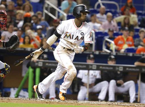FILE - In this Sept. 30, 2017, file photo, Miami Marlins' Dee Gordon hits a single during the fifth inning of a baseball game against the Atlanta Braves in Miami. Gordon has been traded to the Seattle Mariners for three prospects in a deal that marks the start of the Marlins' latest payroll purge, this time under new CEO Derek Jeter.