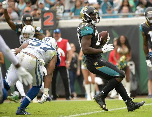 Jacksonville Jaguars running back Leonard Fournette, right, runs for a 5-yard touchdown past Indianapolis Colts outside linebacker Barkevious Mingo (52) during the second half of an NFL football game, Sunday, Dec. 3, 2017, in Jacksonville, Fla.