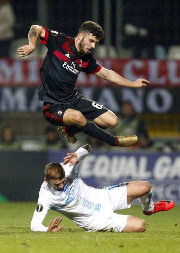 Milan's Patrick Cutrone, top, jumps over Rijeka's Dario Zuparic during the group D Europa League soccer match between Rijeka and Milan, at the Rujevica stadium in Rijeka, Croatia, Thursday, Dec. 7, 2017.