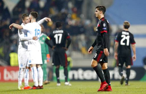 Milan's Andre Silva, right, walks past jubilating Rijeka players at the end of the group D Europa League soccer match between Rijeka and Milan, at the Rujevica stadium in Rijeka, Croatia, Thursday, Dec. 7, 2017.