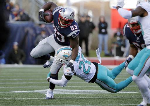 FILE - In this Nov. 26, 2017, file photo New England Patriots tight end Dwayne Allen (83) tries to make yardage as Miami Dolphins free safety Reshad Jones (20) tries to get a grip on him during the first half of an NFL football game, in Foxborough, Mass. With Rob Gronkowski out, New England will turn to Dwayne Allen for Monday's Dec. 11 game against the Dolphins.