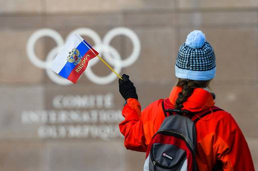 A woman waves a Russian flag outside of the International Olympic Committee (IOC) headquarters in front of the Olympic Rings prior to the opening of the first day of the executive board meeting of the International Olympic Committee (IOC) at the IOC headquarters, in Pully near Lausanne, on Tuesday, Dec. 5, 2017.  Russian athletes will be allowed to compete at the upcoming Pyeongchang Olympics as neutrals despite orchestrated doping at the 2014 Sochi Games, the International Olympic Committee said Tuesday. (Jean-Christophe Bott, Keystone via AP)