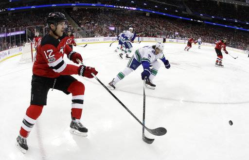 New Jersey Devils defenseman Ben Lovejoy (12) clears the puck as Vancouver Canucks left wing Loui Eriksson (21), of Sweden, tries to get his stick on it during the first period of an NHL hockey game, Friday, Nov. 24, 2017, in Newark, N.J.