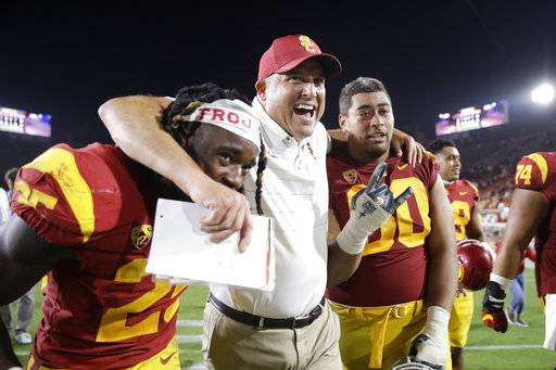 FILE - In this Sept. 9, 2017, file photo, Southern California coach Clay Helton, center, Ronald Jones II, left, and Viane Talamaivao celebrate the team's 42-24 win against Stanford, as they walk off the field after an NCAA college football game in Los Angeles. Helton was selected Pac-12 Coach of the Year, Thursday, Dec. 7, 2017.
