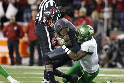 FILE - In this Oct. 1, 2016, file photo, Oregon defensive back Arrion Springs (1) brings down Washington State wide receiver Tavares Martin Jr. (8) during the second half of an NCAA college football game, in Pullman, Wash. Springs was selected to the 2017 AP All-Conference Pac-12 team announced Thursday, Dec. 7, 2017.