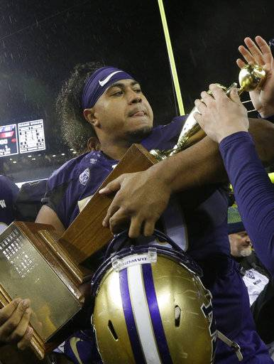 FILE - In this Nov. 25, 2017, file photo, Washington defensive lineman Vita Vea holds the Apple Cup trophy after Washington beat Washington State 41-14 in an NCAA college football game, in Seattle. Vea was selected to the AP All-Conference Pac-12 team announced Thursday, Dec. 7, 2017.