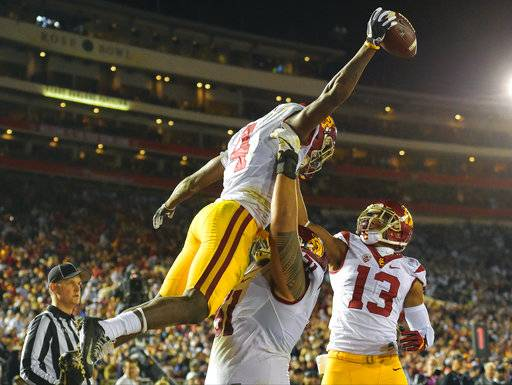 FILE - In this Jan. 2, 2017, file photo, Southern California running back Ronald Jones II, left, celebrates with De'Quan Hampton, right, and Damien Mama after scoring during the second half of the Rose Bowl NCAA college football game against Penn State, in Pasadena, Calif. Jones was selected to the 2017 AP All-Conference Pac-12 team announced Thursday, Dec. 7, 2017.