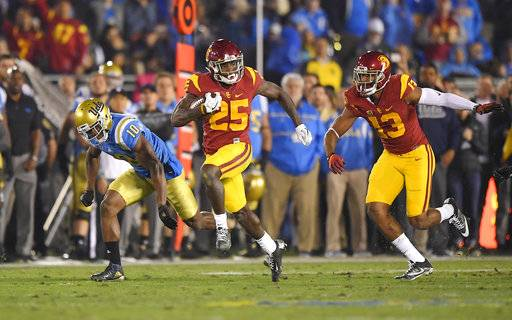 FILE - In this Nov. 19, 2016, file photo, Southern California running back Ronald Jones II, center, runs 60 yards for a touchdown as UCLA defensive back Fabian Moreau, left, runs behind along with wide receiver De'Quan Hampton during the first half of an NCAA college football game, in Pasadena, Calif. Jones was selected to the 2017 AP All-Conference Pac-12 team announced Thursday, Dec. 7, 2017.