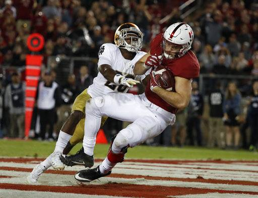 FILE - In this Nov. 25, 2017, file photo, Stanford tight end Kaden Smith (82) catches a touchdown pass in front of Notre Dame cornerback Shaun Crawford (20) during the second half of an NCAA college football game, in Stanford, Calif. Smith was selected to the AP All-Conference Pac-12 team announced Thursday, Dec. 7, 2017.