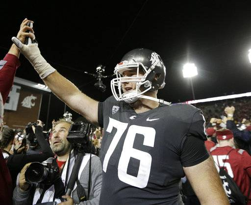 FILE - In this Sept. 29, 2017, file photo, Washington State offensive lineman Cody O'Connell (76) celebrates with fans after his team won an NCAA college football game against Southern California, in Pullman, Wash. O'Connell was selected to the AP All-Conference Pac-12 team announced Thursday, Dec. 7, 2017.