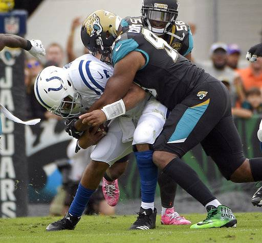 FILE - In this Dec. 3, 2017, file photo, Jacksonville Jaguars defensive lineman Calais Campbell, right, sacks Indianapolis Colts quarterback Jacoby Brissett during the first half of an NFL football game, in Jacksonville, Fla. Jacksonville had been spending millions that seemed wasted until defensive end Calais Campbell, and he easily is the league's best free-agent acquisition of 2017 putting the Jaguars (8-4) in the mix for their first playoff berth since 2007.