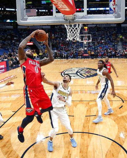 New Orleans Pelicans center DeMarcus Cousins (0) pulls down a rebound over Denver Nuggets guard Jamal Murray in the first half of an NBA basketball game in New Orleans, Wednesday, Dec. 6, 2017.