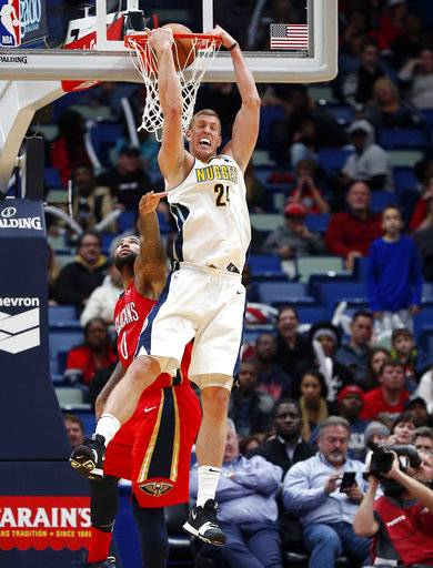 Denver Nuggets center Mason Plumlee (24) slam dunks over New Orleans Pelicans center DeMarcus Cousins (0) in the second half of an NBA basketball game in New Orleans, Wednesday, Dec. 6, 2017. The Pelicans won 123-114.
