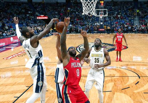 New Orleans Pelicans center DeMarcus Cousins (0) battles under the basket with Denver Nuggets guard Will Barton (5) in the first half of an NBA basketball game in New Orleans, Wednesday, Dec. 6, 2017.