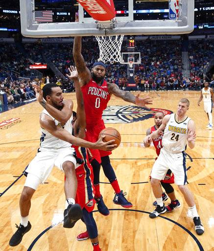 Denver Nuggets forward Trey Lyles passes around New Orleans Pelicans center DeMarcus Cousins (0) in the second half of an NBA basketball game in New Orleans, Wednesday, Dec. 6, 2017. The Pelicans won 123-114.